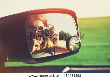 smiling girl taking photo with camera moving in car - stock photo