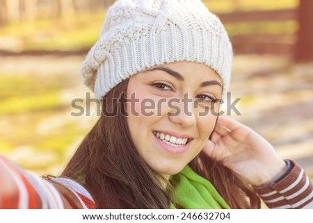 Smiling girl taking selfie with phone outdoor.