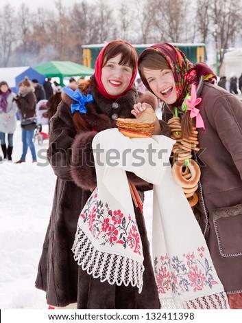 Smiling girl tasting pancake  during  Shrovetide at Russia - stock photo