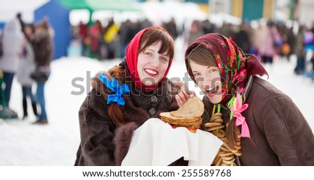 Smiling girl tasting pancake  during  Shrovetide at Russia - stock photo