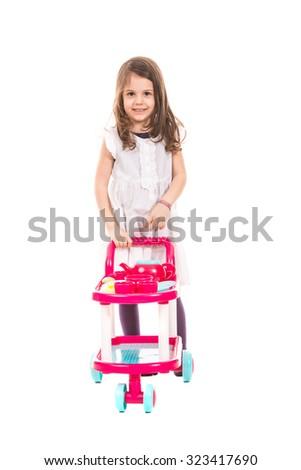 Smiling girl walking and pushing pram toy isolated on white background - stock photo