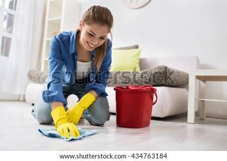 Smiling girl wash the floor with rag and detergent - stock photo
