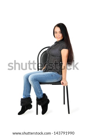 smiling girl wearing blue jeans sits on chair isolated on white background