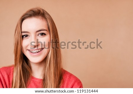 smiling girl wearing braces, candid portrait - stock photo