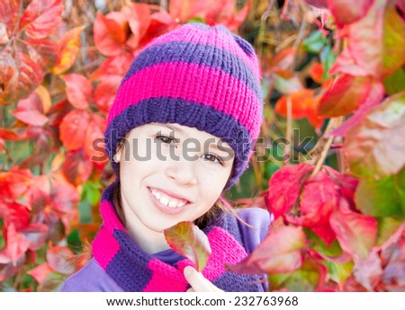 Smiling girl wearing hat and scarf among red autumn leaves - stock photo