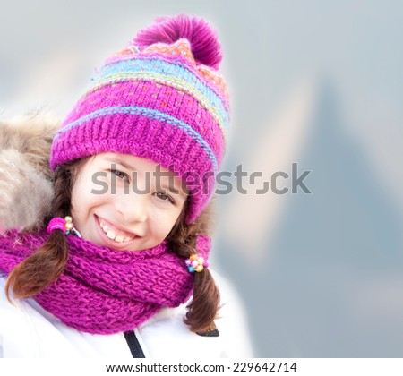 Smiling girl wearing hat and scarf in mountains - stock photo