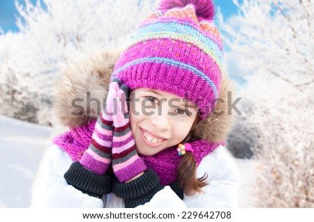 Smiling girl wearing hat, scarf and gloves in winter forest - stock photo