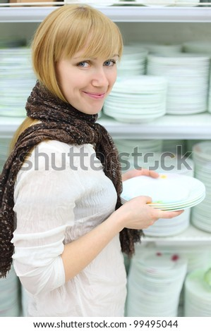 Smiling girl wearing scarf holds some white plates in shop; shallow depth of field - stock photo