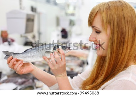 Smiling girl wearing white shirt holds fish in store; shallow depth of field - stock photo