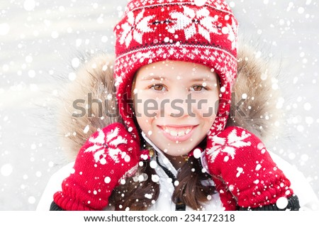 Smiling girl wearing winter clothes under snow - stock photo