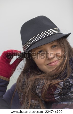 Smiling girl with a black hat and a big scarf, red glove