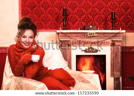 Smiling girl with a cup of coffee in christmas evening in red vintage room studio shot - stock photo