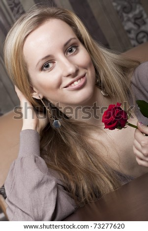 Smiling girl with a red rose - stock photo
