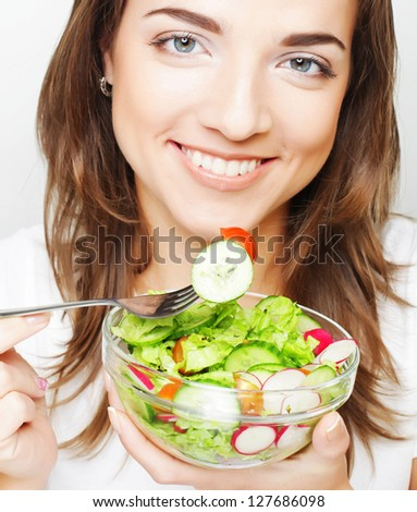 Smiling girl with a salad on a white background - stock photo