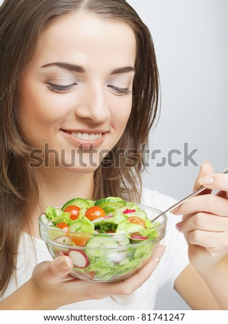 Smiling girl with a salad on a white background