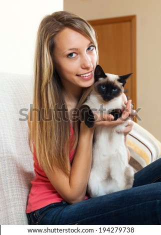 Smiling girl with a Siamese cat in her arms in the room - stock photo
