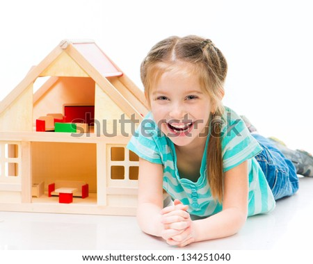 smiling girl with a toy house lying on the floor - stock photo
