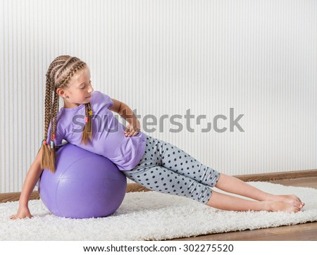 smiling girl with african braids on the ball for fittnes at home - stock photo