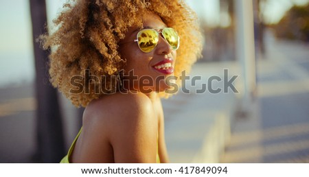 Smiling Girl with Afro Resting on Promenade - stock photo