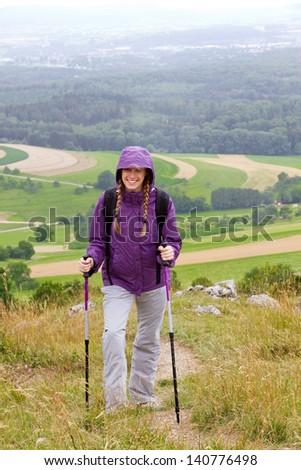 Smiling girl with anorak and hiking sticks walking in rain - stock photo