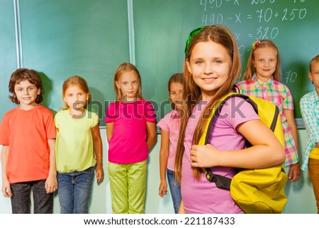 Smiling girl with bag and other pupils behind