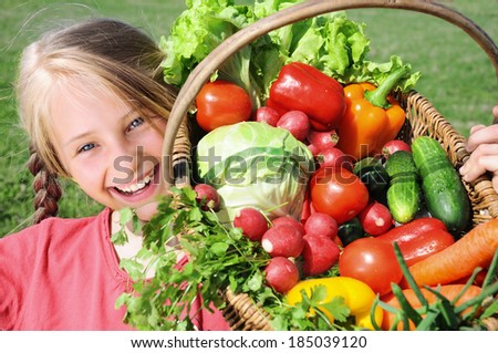 Smiling girl with basket of vegetables - stock photo