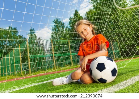 Smiling girl with bending arm on football sitting - stock photo