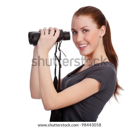 Smiling girl with binoculars posing against white background - stock photo