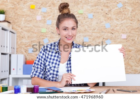 Smiling girl with bun is sitting in office and holding large piece of paper. Concept of advertisement. Mock up