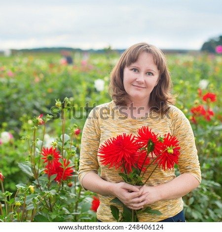 Smiling girl with bunch of red dahlias