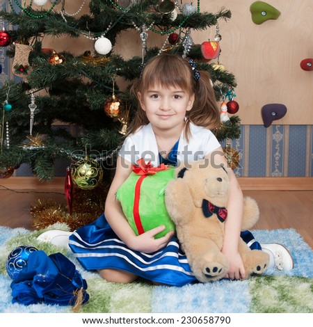 Smiling girl with Christmas gifts at Christmas tree (6 years) - stock photo