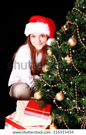 smiling girl with christmas tree and presents over dark background - stock photo