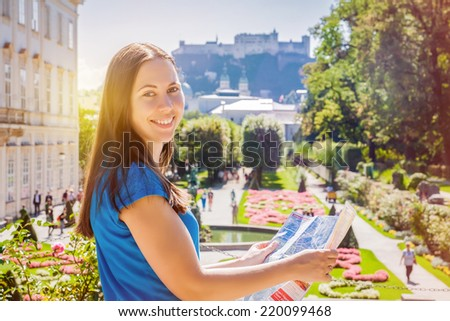 Smiling girl with city map in Mirabell Garden in Salzburg, Austria