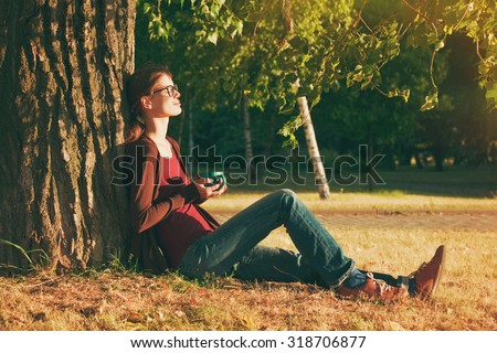 Smiling girl with cup of tea or coffee enjoying near park tree in morning sunlight