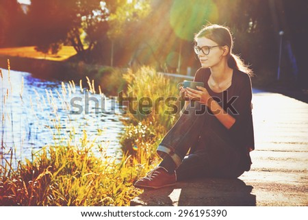 Smiling girl with cup of tea or coffee enjoying on summer shore of river - stock photo