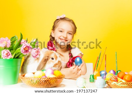 Smiling girl with Eastern eggs and cute rabbit on the table with the yellow background