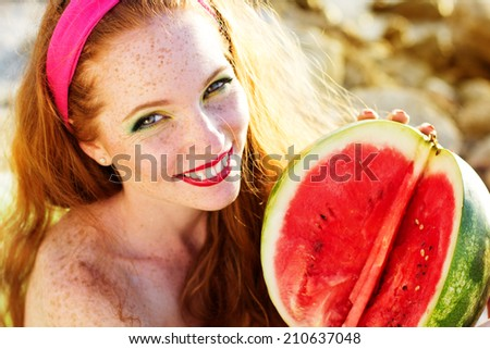 Smiling girl with freckles holding watermelon - stock photo