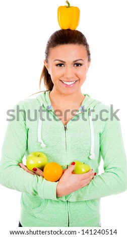 Smiling girl with fruits in arms and balancing bell pepper on head, isolated on white background - stock photo