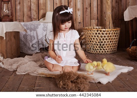 smiling girl with geese, sitting on the wooden floor