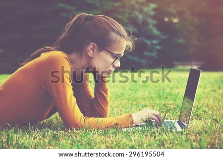 Smiling girl with glasses lying on the grass and using laptop and typing - stock photo
