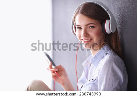 Smiling girl with headphones sitting on the floor - stock photo