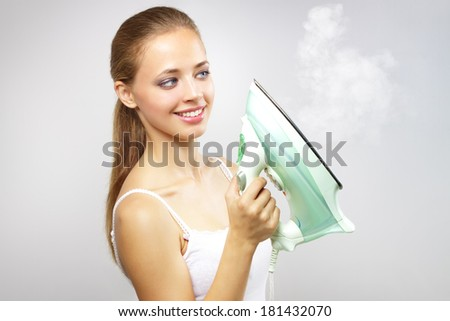 Smiling girl with iron on gray background - stock photo