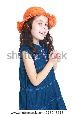 Smiling girl with long black hair wearing an orange hat and long black denim dress is photographed turning to the camera sideways - stock photo