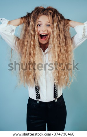 Smiling girl with long blonde hair on blue background