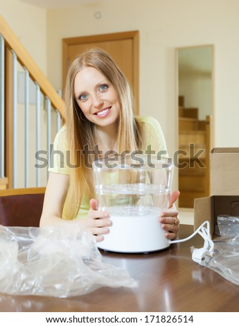 Smiling girl with new electric steamer at home
