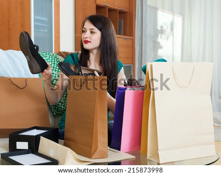 Smiling girl with  purchases at  home
