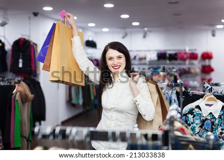 Smiling girl with shopping bags at clothing store - stock photo