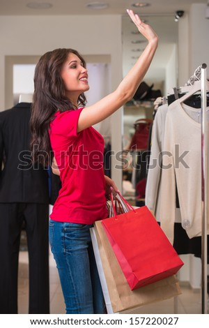 Smiling girl with shopping bags at store waving her hand to friends or sales person for asking help