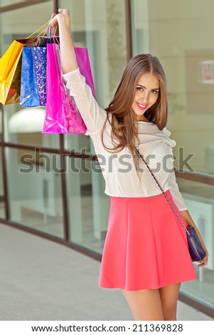 Smiling girl with shopping bags in shop