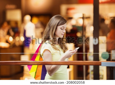 Smiling girl with smartphone in shopping mall - stock photo